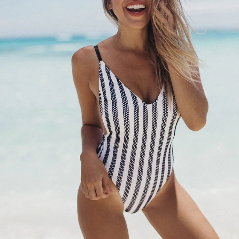 girl on a beach in stripped swimsuit