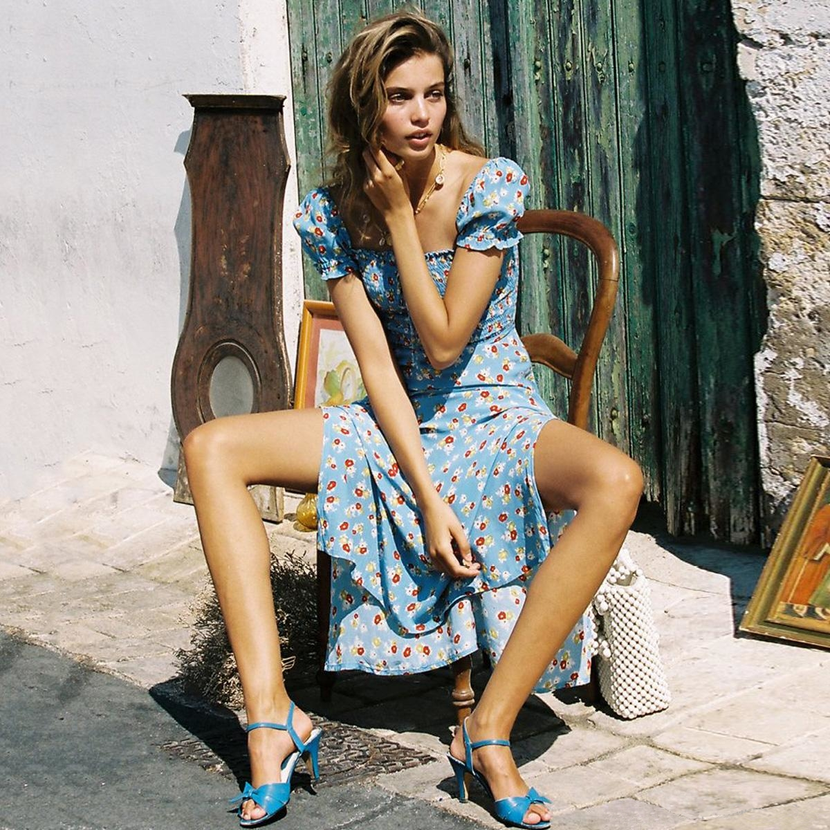 beautiful model is posing on a chair in a blue floral dress